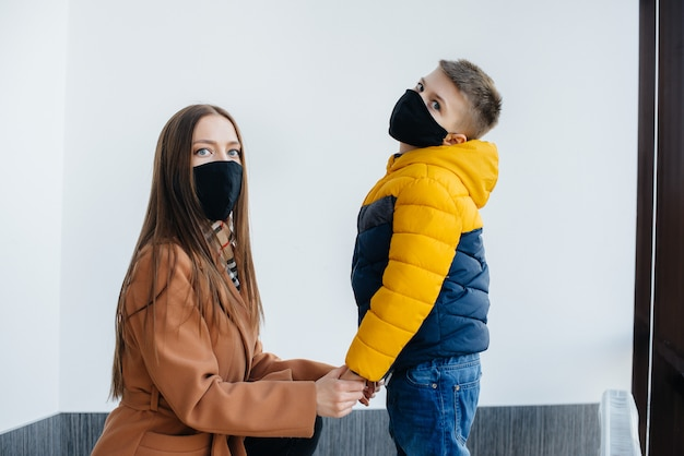 隔離中、子供を持つ母親が仮面に立っています。パンデミック、コロナウイルス。
