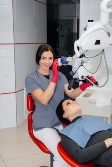 Стоматолог смотрит в микроскоп и выполняет операцию на пациенте.