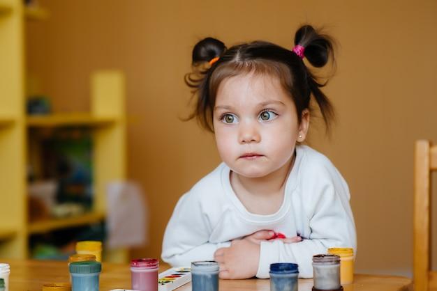 かわいい女の子が遊んでいて、自分の部屋で絵を描いています。レクリエーションとエンターテイメント。