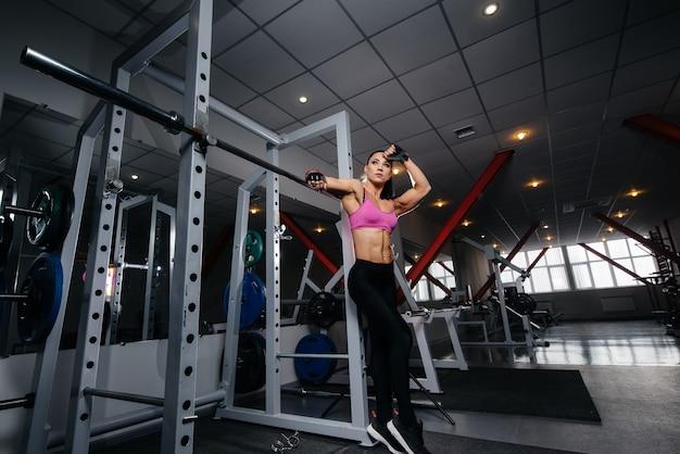 ハードトレーニングの後、ジムでポーズ美しい、運動のセクシーな女の子。フィットネス、ボディービル。