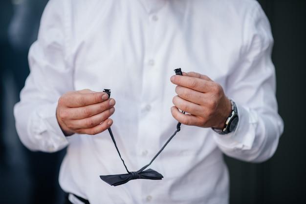 Стильный мужчина держит бабочка крупным планом. мода.