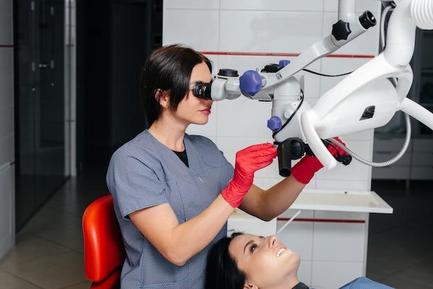 歯科医は顕微鏡をのぞき、患者に手術を行います