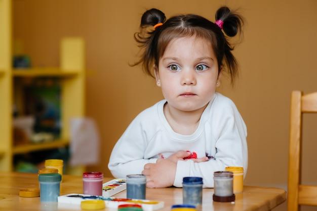 かわいい女の子が彼女の部屋で遊んでいて絵を描いています。レクリエーションとエンターテイメント。