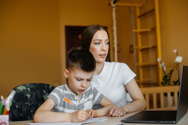 母親と子供は自宅のコンピューターの前で遠隔学習に従事しています。家にいる、トレーニング。