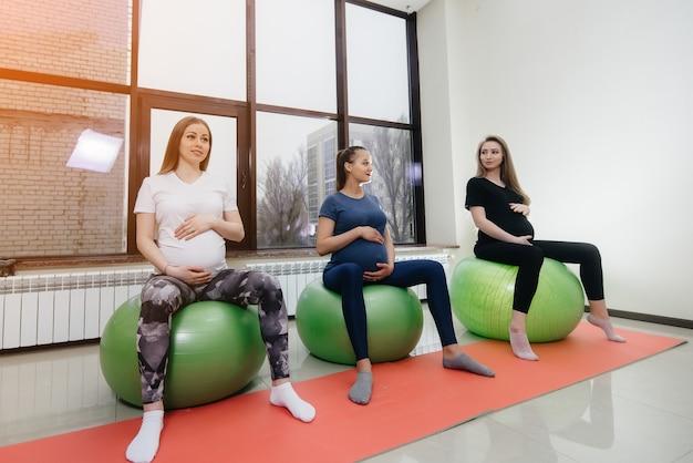 Группа молодых беременных мам занимается пилатесом и мячом в фитнес-клубе. беременные.