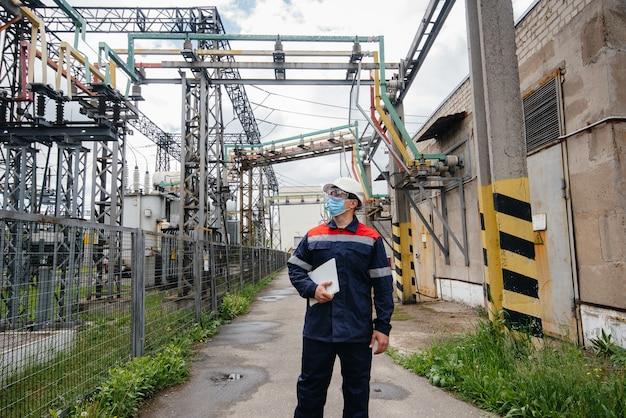 変電所のエンジニアが、ポンデミア時にマスク内の最新の高圧機器を検査します。エネルギー。業界。