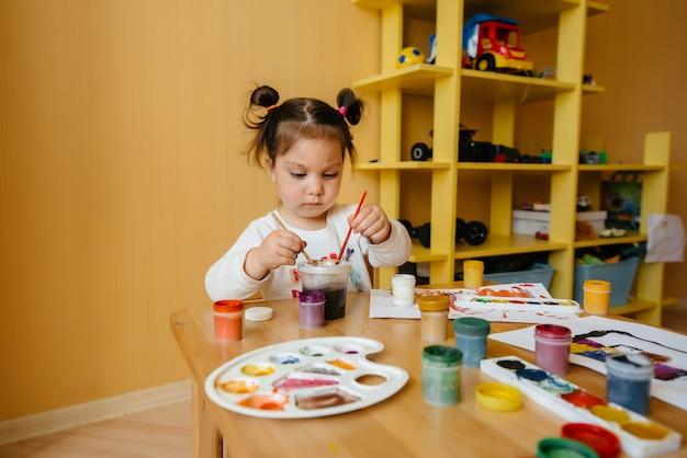 かわいい女の子が自分の部屋で遊んでいて絵を描いています。レクリエーションとエンターテイメント。