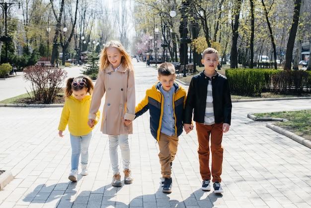 Группа детей играет вместе и гуляет в парке, держась за руки. друзья, дети.