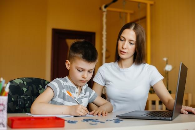 Мать и ее ребенок занимаются дистанционным обучением дома перед компьютером. сиди дома, тренируйся.