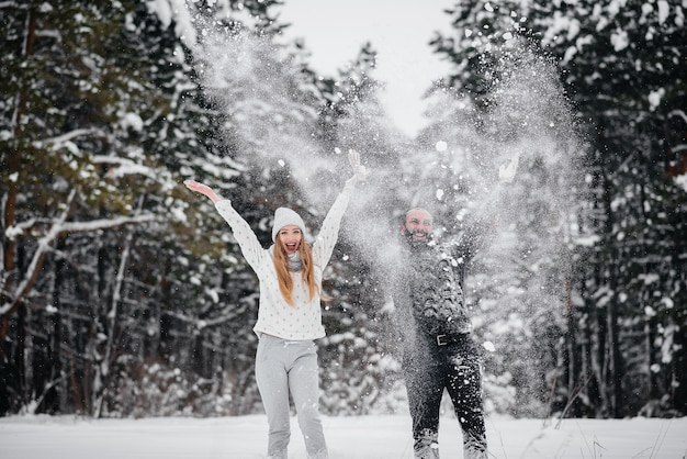 森の中の雪で遊ぶカップル