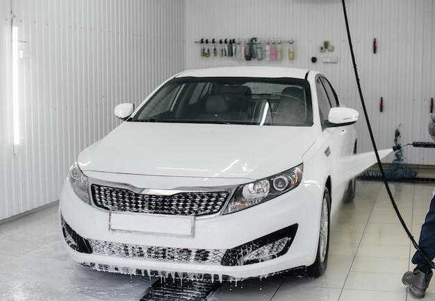 白い車の泡と高圧水による現代の洗浄