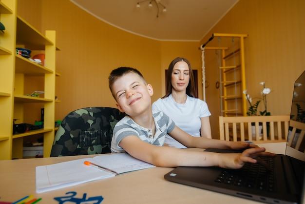 母と子が自宅のコンピューターの前で遠隔教育に従事