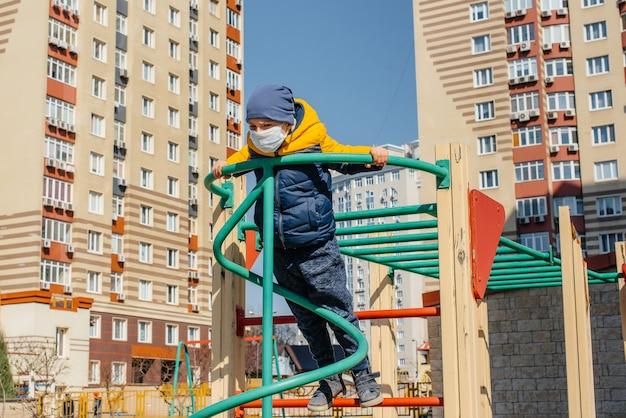 Маленький мальчик в маске гуляет по детской площадке во время карантина. оставайся дома.