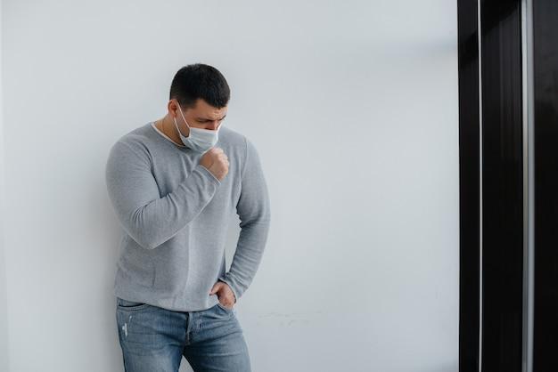 若い男が空きスペースのある検疫中にマスクをかぶった灰色のスペースに立っています。マスクの検疫。