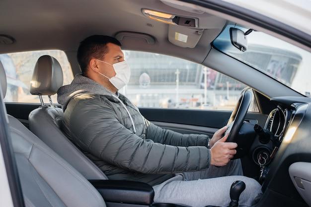 パンデミックとコロナウイルスの最中に運転している間、若い男は個人の安全のためにマスクを着用して車の後ろに座っています。エピデミック。