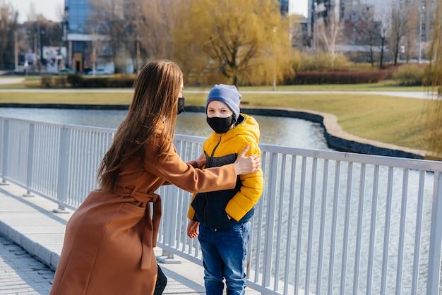 Молодая семья гуляет и дышит свежим воздухом в солнечный день во время карантина и пандемии. маски на лицах людей.