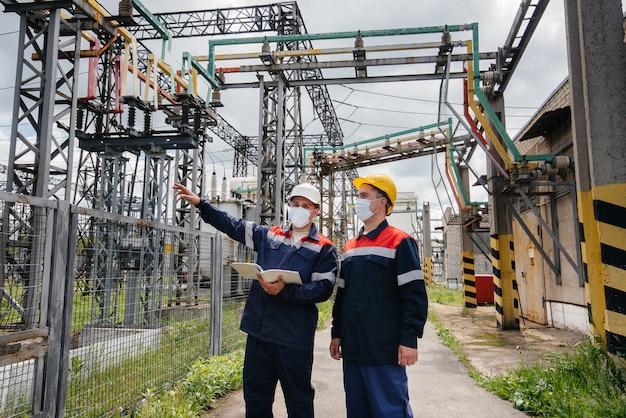 Инженеры электрических подстанций проводят обследование современного высоковольтного оборудования в маске во время пандемии. энергетика. промышленность.