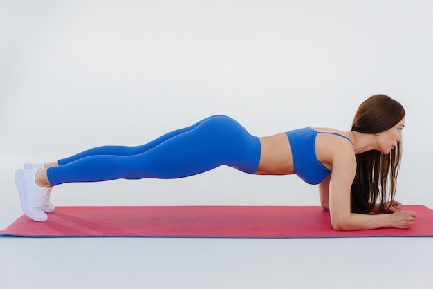 Сексуальная молодая девушка выполняет спортивные упражнения на белой стене. фитнес, здоровый образ жизни.