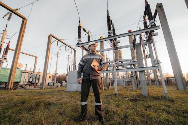 若いエンジニアが変電所の仮面に立っています。