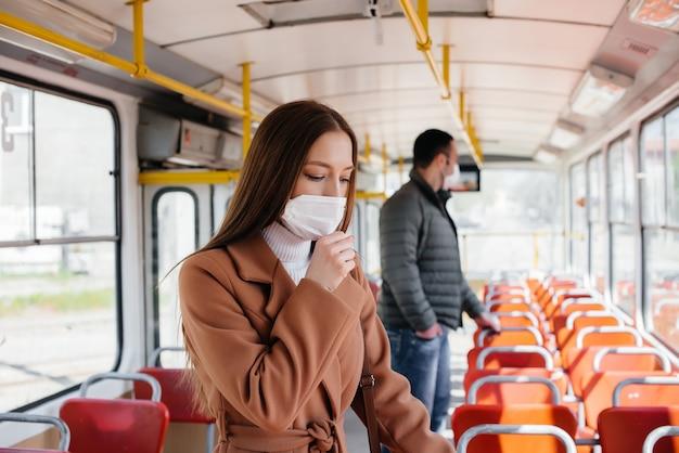 Пассажиры в общественном транспорте во время пандемии коронавируса держатся на расстоянии друг от друга
