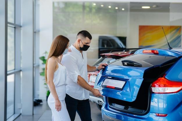 Молодая пара в масках выбирает новое транспортное средство и консультируется с представителем автосалона в период пандемии. продажи автомобилей и жизнь во время пандемии.