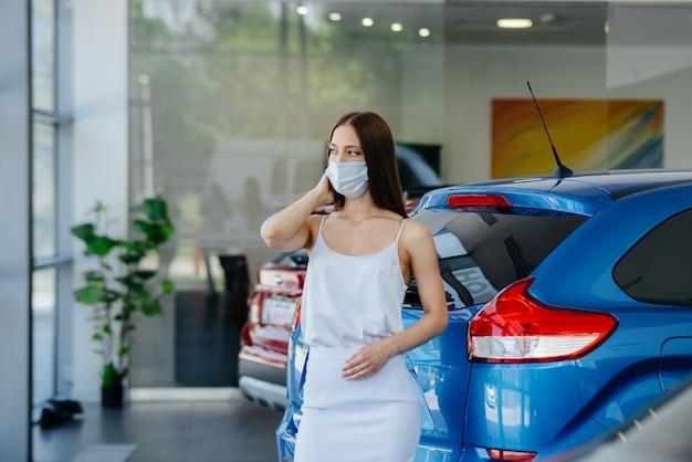 若い可愛い女の子がパンデミックの最中に仮面をかぶった自動車販売店で新車を検査します。パンデミア時代の自動車の売買。