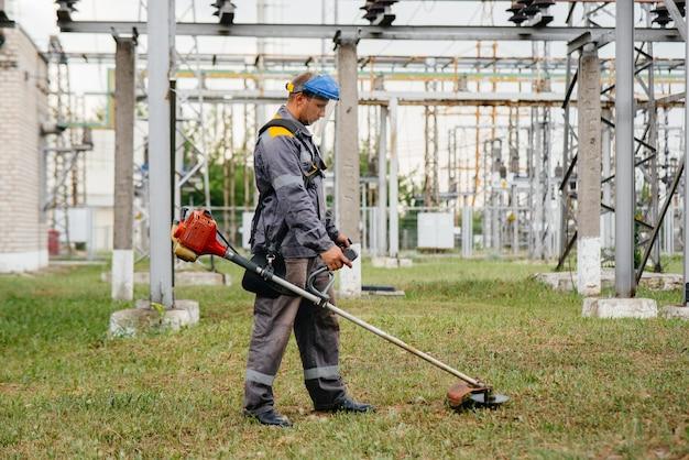 オーバーオールの変電所の領域で草を刈る若い男。企業での草の清掃、火災安全対策の実施。