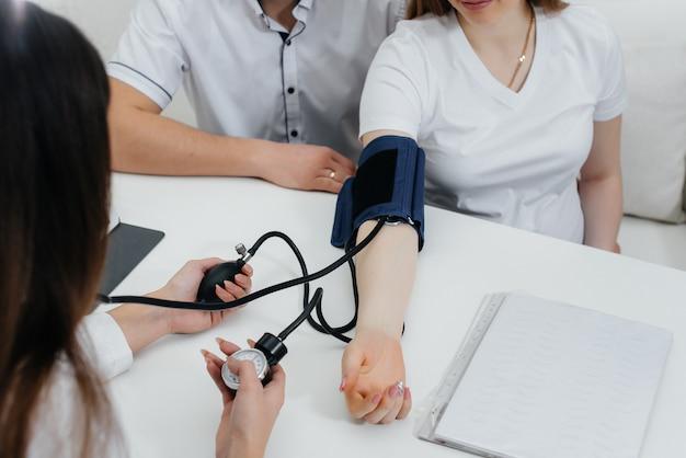 医者はクリニックで妊娠中の女の子の圧力を測定します。妊娠と健康管理