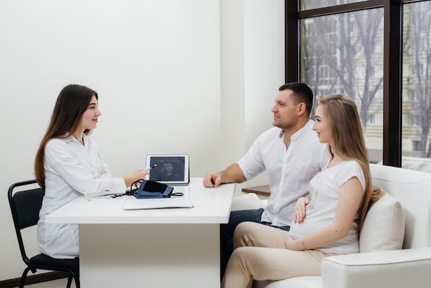 超音波検査の後、赤ちゃんが婦人科医に相談するのを待っている若いカップル。妊娠と健康管理