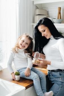 ママと小さな娘はキッチンで料理をして遊ぶ。家族、幸せ。