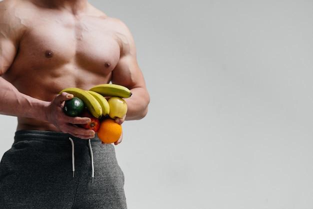 果物のアスリートのスポーティな裸の胴体。フィットネス。健康的なダイエット