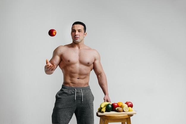 明るい果物でポーズスポーティなセクシーな男。ダイエット。健康的なダイエット