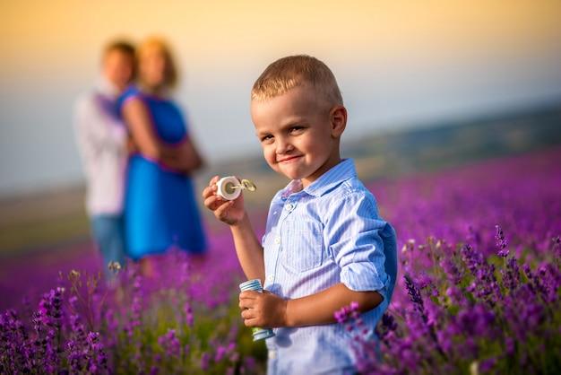 Счастливая семья с маленьким мальчиком гуляет и играет на прекрасном лавандовом поле. семейный отдых