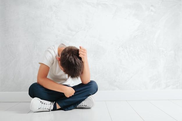 Ребенок, чья депрессия сидит на полу