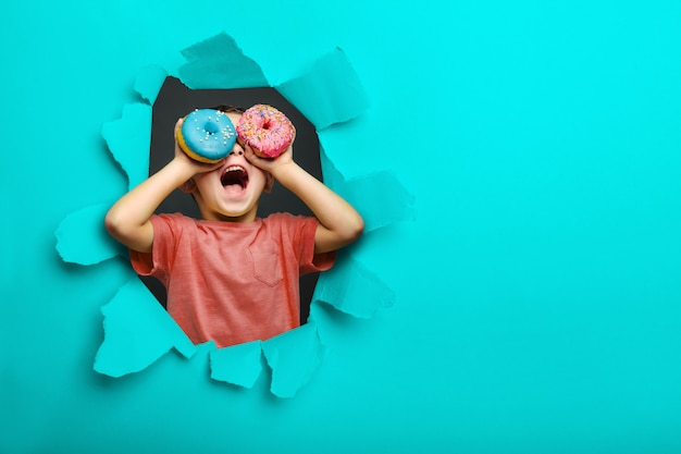 幸せなかわいい男の子は黒い背景の壁にドーナツで遊んで楽しんでいます。子供の明るい写真。