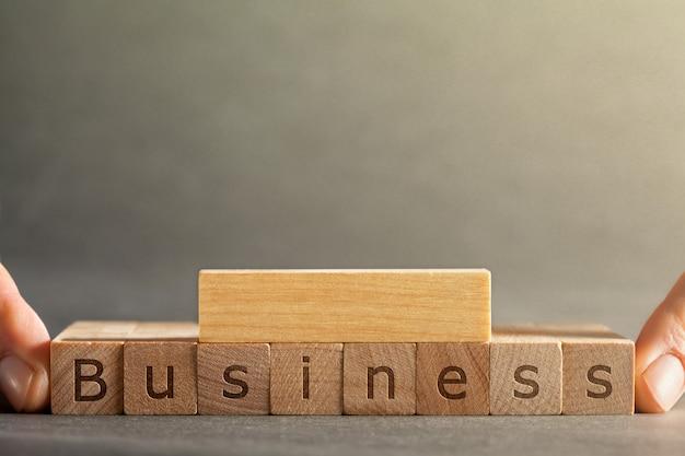 Онлайн бизнес надпись выгравирована на блоках, которые держат пальцы на сером фоне