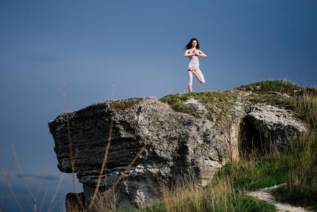 岩の上の複雑なヨガの練習を行う若い女性
