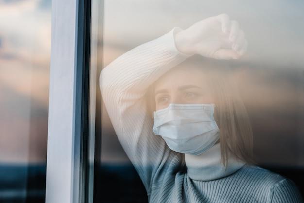 コロナウイルス。窓から見ている保護マスクを身に着けている病気の女性。感染を防ぐために患者を家に隔離した。病院の検疫室。