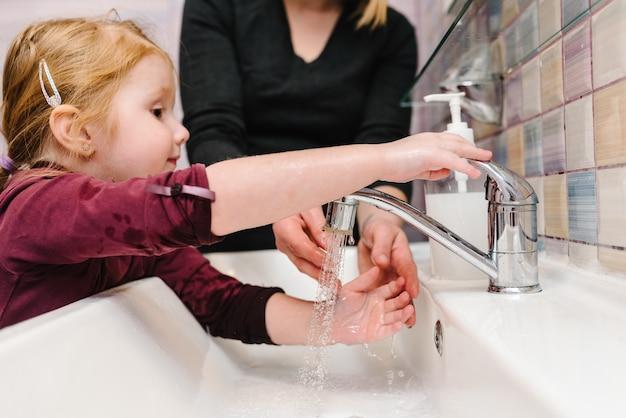 小さな女の子がバスルームのシンクで手を洗います。手を洗う