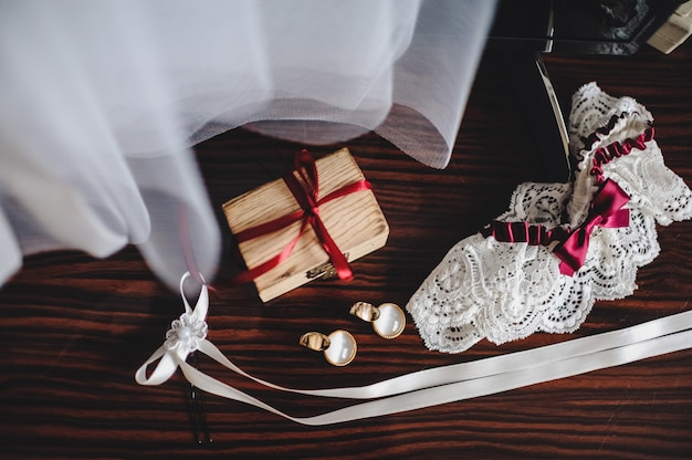 結婚式のアクセサリー、ドレス、イヤリング、ボックス、ガーター、茶色のテーブルの上に横たわる