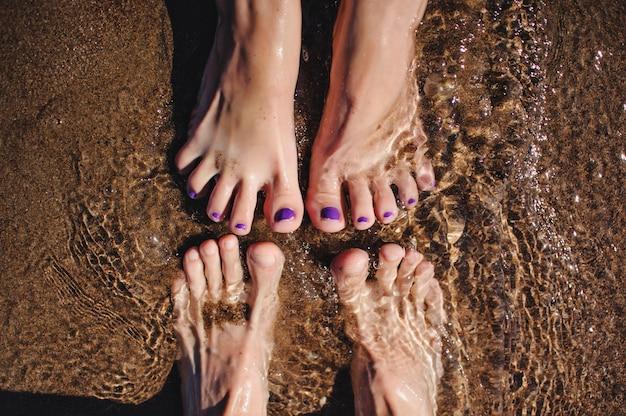 砂の中の水で美しい男性と女性の足。海のビーチ。