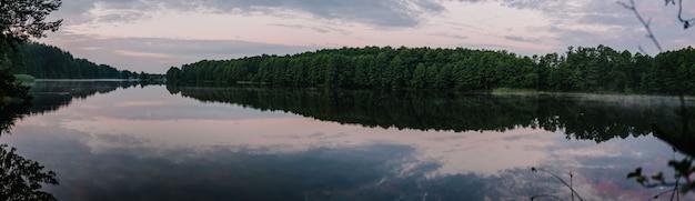 春の木のパノラマ写真と湖。湖の静かな風景。