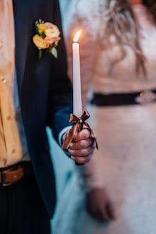 新郎は茶色の弓で結婚式のキャンドルを保持しています。