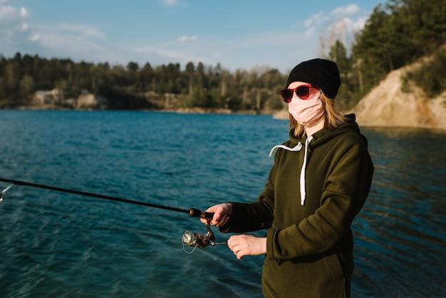 湖の銀行にリールを回転を持つ漁師
