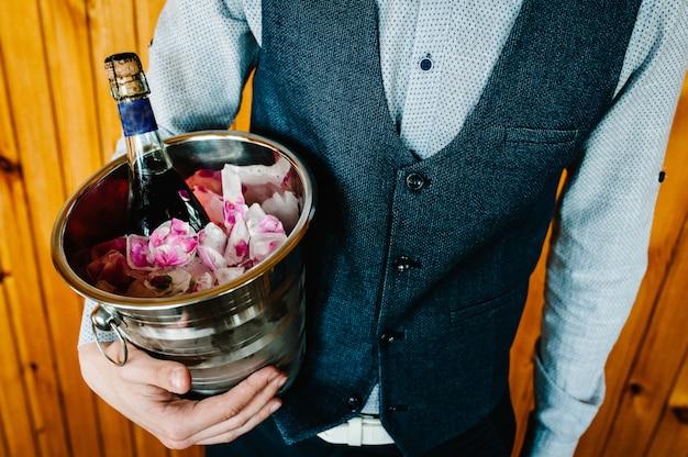 Стильный счастливый жених держит ведро льда и шампанского. с лепестками роз в кубиках льда.