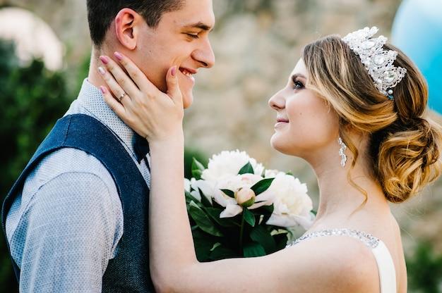 Стильная счастливая невеста и жених. молодожены обнимаются.