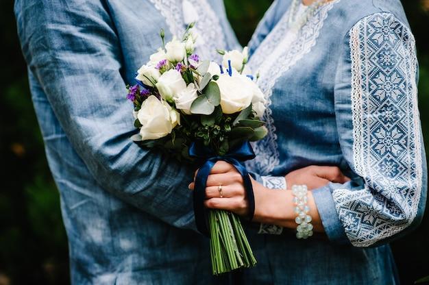 ブッシュのバラ、トルコギキョウ、手でスタイリッシュな花嫁の女性が刺繍のドレスと新郎のシャツを着たウェディングブーケフラワーは、ブーケを保持しています。結婚式。閉じる。