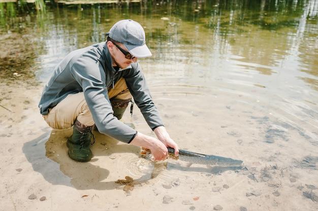 Рыбак выпускает под воду большую рыбу, большую щуку в пруду. спортивная рыбалка. мужчина держит щуку в озере.