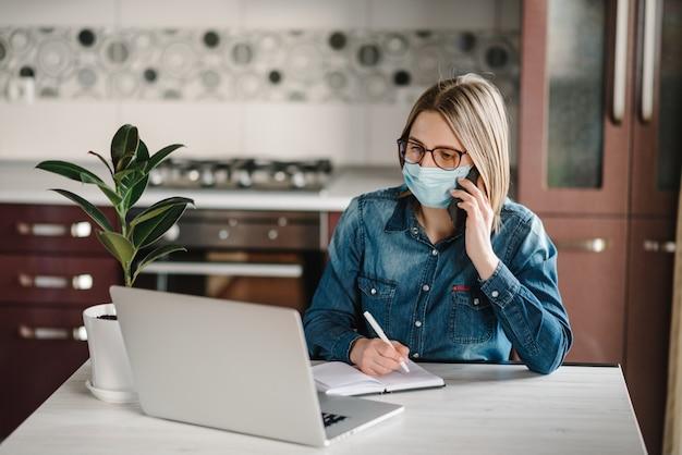 コロナウイルス。ビジネスの女性が働いて、電話で話して、検疫に防護マスクを着ています。家にいる。女の子は、ホームオフィスでラップトップコンピューターを使用して学習します。フリーランス。書く、タイプする。