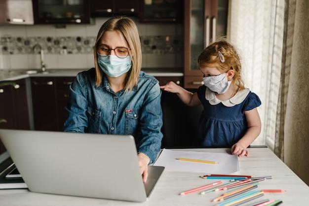 コロナウイルス。ママと娘が検疫で保護マスクを着用しています。